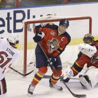 Photo - Ottawa Senators right wing Mark Stone (61) scores a goal against Florida Panthers defenseman Ed Jovanovski (55) and goalie Roberto Luongo (1) during the second period of an NHL hockey game, Tuesday, March 25, 2014 in Sunrise, Fla. (AP Photo/Wilfredo Lee)