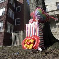 Photo - FILE - In this March 12, 2013 file photo, a makeshift memorial is seen in Chicago at the site where 6-month-old girl Jonylah Watkins, and her father, a known gang member, were shot Monday, March 11. Chicago Police Superintendent Gary McCarthy said Monday, March 18, 2013, that Jonylah Watkins was sitting in Jonathon Watkins' lap in the driver's seat of a minivan when the shooter approached the vehicle and fired. That's a change from previous reports that Watkins was changing the baby's diaper at the time. McCarthy also says the baby was shot once, not several times as previously reported. (AP Photo/M. Spencer Green, File)