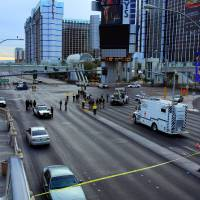 Photo - FILE - In this Feb. 21, 2013 file photo, law enforcement personal investigate the scene of a multi-vehicle accident and shooting in Las Vegas. Variously known as an adult playground and Disneyland for grown-ups, Las Vegas has worked to brand itself as a place where tourists can enjoy a sense of edginess with no real danger. But a series of high-profile and seemingly random incidents that have left visitors to the Strip dead or in the hospital is threatening Sin City's reputation as a padded room of a town where people can cut loose with no fear of consequences. (AP Photo/Las Vegas Review-Journal, Jeff Scheid, File) LOCAL TV OUT; LOCAL INTERNET OUT; LAS VEGAS SUN OUT
