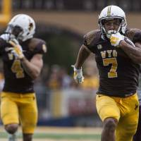 Photo - Wyoming's D.J. May runs in for a Cowboy touchdown as Wyoming hosted  Montana in a NCAA college football game on Saturday, Aug. 30, 2014, at War Memorial Stadium in Laramie, Wyo. (AP Photo/Casper Star-Tribune, Ryan Dorgan)