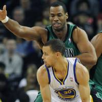 Photo - Golden State Warriors' Stephen Curry, foreground, looks for a receiver under the arm of Boston Celtics' Jason Collins during the first half of an NBA basketball game in Oakland, Calif., Saturday, Dec. 29, 2012. (AP Photo/George Nikitin)