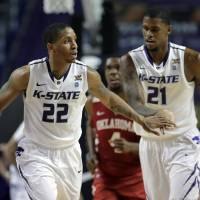 Photo - Kansas State guard Rodney McGruder (22) and forward Jordan Henriquez (21) celebrate after McGruder made a basket during the first half of an NCAA college basketball game against the Oklahoma Saturday, Jan. 19, 2013, in Manhattan, Kan. (AP Photo/Charlie Riedel)