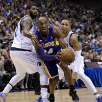 Photo - Los Angeles Lakers guard Kobe Bryant (24) drives against Dallas Mavericks' O.J. Mayo, left, and Shawn Marion, right, in the first half of an NBA basketball game Sunday, Feb. 24, 2013, in Dallas. (AP Photo/Tony Gutierrez)