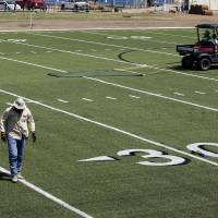 Photo - Workers install artificial turf on the practice field at Moore High School on Thursday.  Photo by Steve Sisney, The Oklahoman