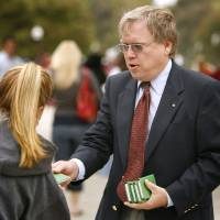 Photo - James Howell, Edmond and a member of the Christian group Gideons International, passes out free New Testaments on the campus of the University of Oklahoma in Norman, Oklahoma on Wednesday October 18, 2006.   Photo by Steve Sisney/The Oklahoman