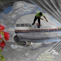 Photo - FILE - In this April 8, 2014, file photo a school utility worker mops a mural depicting the missing Malaysia Airlines Flight 370 at the Benigno