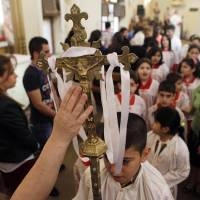 Photo - A worshipper reaches to touch a crucifix during Easter mass at Virgin Mary Chaldean Church in Baghdad, Iraq, Sunday, March 31, 2013. The Chaldean Church is an Eastern Rite church affiliated with the Roman Catholic Church. (AP Photo/ Khalid Mohammed)