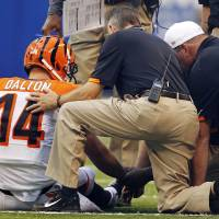 Photo -   Cincinnati Bengals quarterback Andy Dalton (14) is checked by team personnel after taking a hit from the Indianapolis Colts in the first half of an NFL preseason football game in Indianapolis, Thursday, Aug. 30, 2012. (AP Photo/John Sommers II)