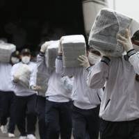 Photo - Police carry blocks of seized cocaine as they present it to the press at a police base in Lima, Peru, Monday, Sept. 1, 2014. Police announced that they seized 7.7 metric tons (8.5 tons) of cocaine in the northern town of Trujillo on Aug. 26, and that it's the largest seizure of cocaine in Peru's history. (AP Photo/Martin Mejia)