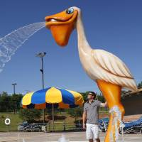 Photo - Jared Prince stands under the new pelican shower at the Pelican Bay Aquatic Center on Wednesday in Edmond.  Photos by Jim Beckel, THE OKLAHOMAN