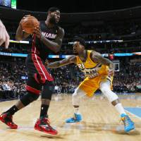 Photo - Miami Heat forward LeBron James, left, works the ball inside as Denver Nuggets forward Wilson Chandler defends in the first quarter of an NBA basketball game in Denver on Monday, Dec. 30, 2013. (AP Photo/David Zalubowski)