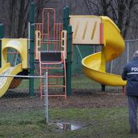 Photo - Police investigate the playground in Upper Darby, Pa., where a 5-year-old girl wearing only a T-shirt was found hiding under a piece of playground equipment early Tuesday morning, Jan. 15, 2013. The girl had been abducted Monday morning from the William C. Bryant School, in west Philadelphia, by a woman claiming to be her mother. (AP Photo/Philadelphia Daily News, Alejandro A. Alvarez)  THE EVENING BULLETIN OUT, TV OUT; MAGS OUT; NO SALES