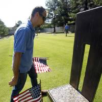 Photo -  James Sing of Midwest City places flags next to each of the chair monuments at the Oklahoma City bombing memorial on Monday, July 1, 2013. Photo by Aliki Dyer/The Oklahoman