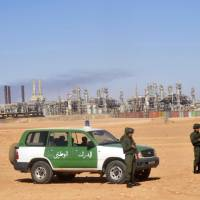 Photo - FILE - This  Jan. 31, 2013, file photo shows Algerian soldiers standing guard during a visit for news media organized by the Algerian authorities at the gas plant in Ain Amenas, seen on background. New corruption scandals are shining a fresh spotlight on Sonatrach, which jointly with BP and Norway's Statoil runs the desert gas plant that was the scene of a bloody hostage standoff last month. (AP Photo/File)