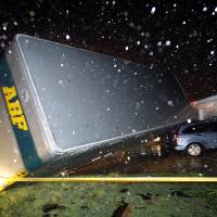 Photo - A trucking company trailer landed on a car that was parked in front of a Lindsey Ln. home in Cleburne Texas after a powerful storm went through Wednesday night, May 15, 2013. Neighbors say the trailer was parked on the street and was rolled over onto the car. (AP Photo/The Dallas Morning News, Tom Fox)