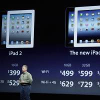 Photo -   Apple's senior vice president of Worldwide Marketing Phil Schiller talks about new pricing for the iPad2, left, and the new iPad, right, during an Apple event in San Francisco, Wednesday, March 7, 2012. The new iPad features a sharper screen and a faster processor. Apple says the new display will be even sharper than the high-definition television set in the living room. (AP Photo/Paul Sakuma)