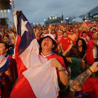 Photo - Soccer fans celebrate as they watch a live broadcast of Chile's Charles Aranguiz scoring his side's second goal against Spain, inside the FIFA Fan Fest area on Copacabana beach, in Rio de Janeiro, Brazil, Wednesday, June 18, 2014. Chile defeated Spain 2-0 in their group B World Cup match. (AP Photo/Leo Correa)