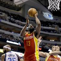 Photo - Houston Rockets' James Harden (13) is fouled going to the basket between Dallas Mavericks' Vince Carter (25) and Rockets' Donatas Motiejunas (20), of Lithuania, in the first half of an NBA basketball game, Wednesday, March 6, 2013, in Dallas. (AP Photo/Tony Gutierrez)
