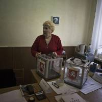 Photo - A Ukrainian woman, who is a member of the district electoral committee, holds a ballot box during preparations for Sunday's referendum at a polling station in Simferopol, Ukraine, Saturday, March 15, 2014. Tensions are high in the Black Sea peninsula of Crimea, where a referendum is to be held Sunday on whether to split off from Ukraine and seek annexation by Russia. (AP Photo/Manu Brabo)