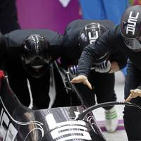 Photo - The team from the United States USA-1, piloted by Steven Holcomb, start a run during the men's four-man bobsled training at the 2014 Winter Olympics, Thursday, Feb. 20, 2014, in Krasnaya Polyana, Russia. (AP Photo/Michael Sohn)
