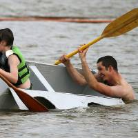 Photo -  Nathaniel Stephenson, right, and his son Maverick, 10, try to keep Hope it Floats afloat during the pair's second time to compete in the annual Cardboard Boat Regatta at Arcadia Lake. The regatta is part of the Edmond's LibertyFest events. PHOTO BY BRYAN TERRY, THE OKLAHOMAN   Bryan Terry -  THE OKLAHOMAN