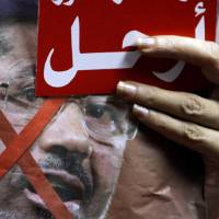 Photo - An Egyptian protester holds anti-President Mohammed Morsi poster and a red card with Arabic word