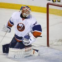 Photo - New York Islanders goalie Anders Nilsson, of Sweden, looks back at his net as Calgary Flames' Joe Colborne, not shown, scores the game winning goal during third period NHL hockey action in Calgary, Alberta, Friday, March 7, 2014. (AP Photo/The Canadian Press, Jeff McIntosh)