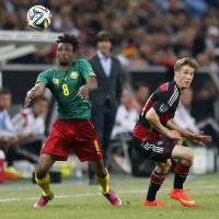 Photo - Germany's Erik Durm, right, and Cameroon's Benjamin Moukandjo challenge for the ball during a soccer friendly match between Germany and Cameroon in Moenchengladbach, Germany, Sunday, June 1, 2014. (AP Photo/Michael Probst)