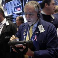 Photo - FILE - In this Wednesday, Dec. 18, 2013, file photo, trader Warren Meyers, center, works on the floor of the New York Stock Exchange. Investors continued Friday, Dec. 20, 2013 to breathe a sigh of relief that the U.S. central bank has committed to keeping interest rates low even though it has decided to start pulling back on its monetary stimulus. (AP Photo/Richard Drew, File)