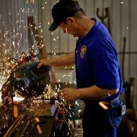 Photo -  World champion horseshoer Mark Milster cuts a steel bar at his shop in Goldsby. Photo by Chris Landsberger, The Oklahoman   CHRIS LANDSBERGER -  CHRIS LANDSBERGER