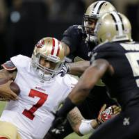 Photo - San Francisco 49ers quarterback Colin Kaepernick (7) slides as he is covered by New Orleans Saints defensive end Cameron Jordan and outside linebacker Ramon Humber (53) in the first half of an NFL football game in New Orleans, Sunday, Nov. 17, 2013. (AP Photo/Bill Haber)