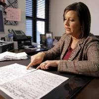 Photo - Courtney McClure looks over an accident report and medical bills in her Oklahoma City office, Wednesday, Feb. 4, 2009. McClure was in an accident with an  uninsured motorist in 2006. PHOTO BY BRYAN TERRY