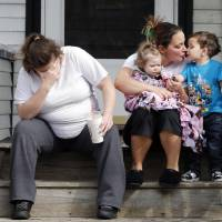 Photo - Neighbors sit outside the house of Krystle Campbell's parents in Medford, Mass.,Tuesday, April 16, 2013. Campbell was killed in Monday's explosions at the finish line of the Boston Marathon. (AP Photo/Michael Dwyer)