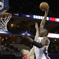 Photo - Charlotte Bobcats' Bismack Biyombo, right, shoots over Houston Rockets' Cole Aldrich, left, during the first half of an NBA basketball game in Charlotte, N.C., Monday, Jan. 21, 2013. (AP Photo/Chuck Burton)