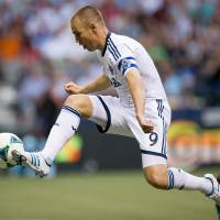 Photo - Vancouver Whitecaps' Kenny Miller, of Scotland, knocks the ball down and moves in to score a goal against the Seattle Sounders during the first half of an MLS soccer  match in Vancouver, British Columbia, on Saturday, July 6, 2013. (AP Photo/The Canadian Press, Darryl Dyck)
