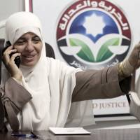 Photo -   In this Wednesday, Oct. 9, 2012 photo, Azza el-Gharf of the Muslim Brotherhood's Freedom and Justice Party talks on her mobile phone at the party's office in Cairo, Egypt. El-Garf, a 47-year-old mother of seven who joined the Brotherhood when she was 15, said that a woman's role in her family need not contradict with her participation in politics, saying that she balances these two responsibilities. The rise of the Muslim Brotherhood to power in Egypt has brought with it a new group of female politicians who say they are determined to bring more women into leadership roles _ and at the same time want to consecrate a deeply conservative Islamic vision for women in Egypt.(AP Photo/Maya Alleruzzo)