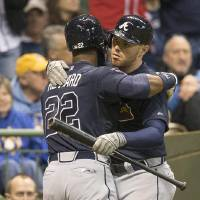 Photo - Atlanta Braves' Jason Heyward is greeted by teammate Freddie Freeman after Heyward hit a two run homer off of Milwaukee Brewers' Kyle Lohse during the fifth inning of a baseball game Tuesday, April 1, 2014, in Milwaukee. (AP Photo/Tom Lynn)