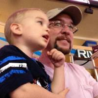 Photo - Altus cotton farmer Danny Robbins and grandson Axel enjoy a Thunder game at the Chesapeake Energy Arena.  provided