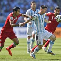 Photo - Iran's Mehrdad Pooladi, left, holds Argentina's Lionel Messi during the group F World Cup soccer match between Argentina and Iran at the Mineirao Stadium in Belo Horizonte, Brazil, Saturday, June 21, 2014. (AP Photo/Martin Meissner)