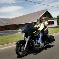 Photo - John Sanders and Gay Sanders prepare for the 2013 National Ride to Work Day for motorcyclists on Monday. Photo by KT KING, The Oklahoman  KT King