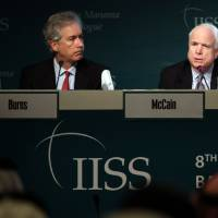Photo - Deputy Secretary of States William Burns, left, and Sen. John McCain, right, answer questions during the International Institute of Strategic Studies (IISS) conference in Manama, Bahrain, Saturday, Dec. 8, 2012. The IISS Manama conference will discuss the security situation in the Syrian region among other topics. (AP Photo/Hasan Jamali)