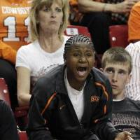 Photo - Serving a one-game tournament suspension, Oklahoma State's  Andrea  Riley cheers on her teammates from the stands as they play Chattanooga during the first half of an NCAA college first-round basketball game in Tempe, Ariz., Saturday, March 20, 2010. (AP Photo/Ross D. Franklin)