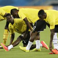 Photo - Ghana players, from left, Albert Adomah, Daniel Opare, Mubarak Wakaso and Christian Atsu stretch during an official training session the day before the group G World Cup soccer match between Ghana and the United States at the Arena das Dunas in Natal, Brazil, Sunday, June 15, 2014. (AP Photo/Dolores Ochoa)