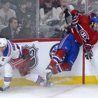Photo - Montreal Canadiens' Brandon Prust, right, collides with New York Rangers' Dan Girardi during the third period of an NHL hockey game in Montreal, Saturday, Feb. 23, 2013. The Canadiens won 3-0.(AP Photo/The Canadian Press, Graham Hughes)