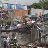 Photo - Firefighters work at the site where a helicopter crashed into a residential area of Sao Paulo, Brazil, Monday, Jan. 21, 2013. According to authorities, the pilot flying the private helicopter died, and three passengers were injured. (AP Photo/Andre Penner)