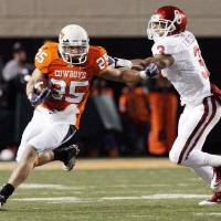 Photo - OSU's Josh Cooper (25) takes a reception past OU's Jonathan Nelson (3) during the 2010 Bedlam football game. The Bedlam football game is moving to December for the 2011 season. Photo by Nate Billings, The Oklahoman  NATE BILLINGS