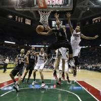 Photo - San Antonio Spurs' Danny Green (4) shoots against Milwaukee Bucks' Monta Ellis (11) during the second half of an NBA basketball game on Wednesday, Jan. 2, 2013, in Milwaukee. (AP Photo/Morry Gash)