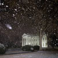 Photo - Snow falls at the White House shortly after President Barack Obama returned from the U.S. Capitol where he made his State of the Union speech in Washington, Tuesday Jan. 28, 2014. (AP Photo/Jacquelyn Martin)