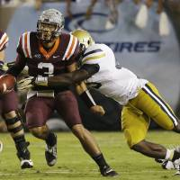Photo - Virginia Tech quarterback Logan Thomas (3) is brought down by Georgia Tech defensive end Jeremiah Attaochu after a short gain in the first half of an NCAA college football game on Thursday, Sept. 26, 2013, in Atlanta. (AP Photo/John Bazemore)