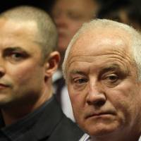 Photo - Olympic athlete Oscar Pistorius' father Henke Pistorius, right, with his son Carl watch as Oscar Pistorius walks in during his bail hearing at the magistrate court in Pretoria, South Africa, Friday, Feb. 22, 2013. (AP Photo/Themba Hadebe)